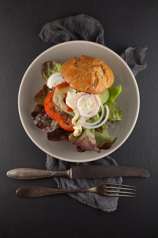 Delicious home made hamburger served on a plate. Rustic slate kitchen table stock photos