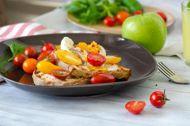 A delicious home style breakfast with eggs, toasted bread, , green apple,colorfull tomatoes, parsley and mint, royalty free stock photo