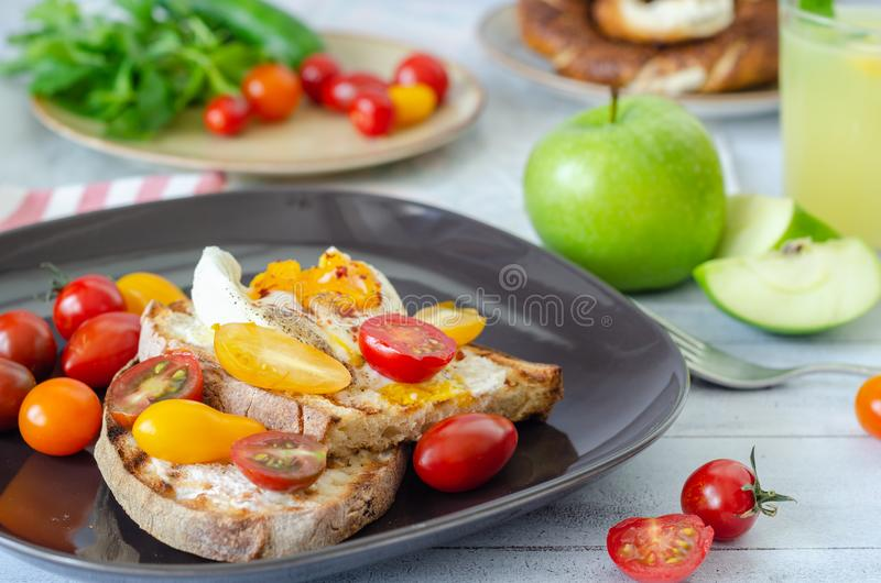 A delicious home style breakfast with eggs, toasted bread, , green apple,colorfull tomatoes, parsley and mint, stock photos