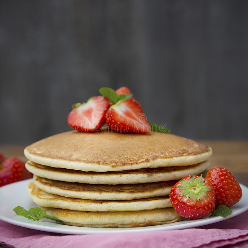 Delicious homemade american pancakes with fresh strawberry and honey. Wooden rustic background. Square image stock images
