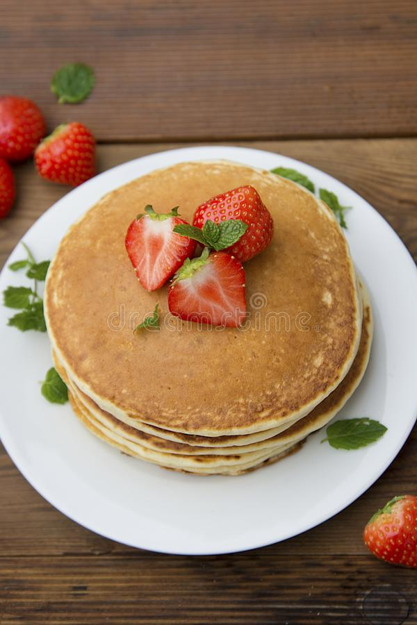 Delicious homemade american pancakes with fresh strawberry and honey. Wooden rustic background. Vertical image, top view stock photo