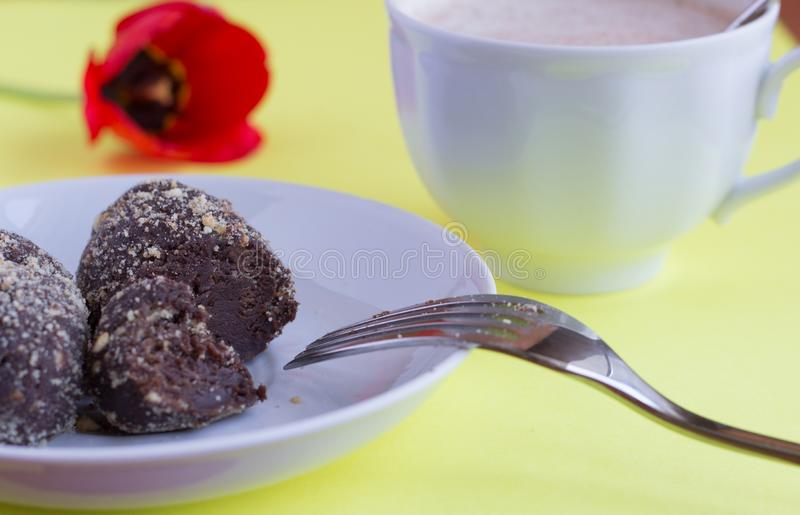 Delicious homemade cakes `potato` and coffee with milk on a yellow background.  stock image