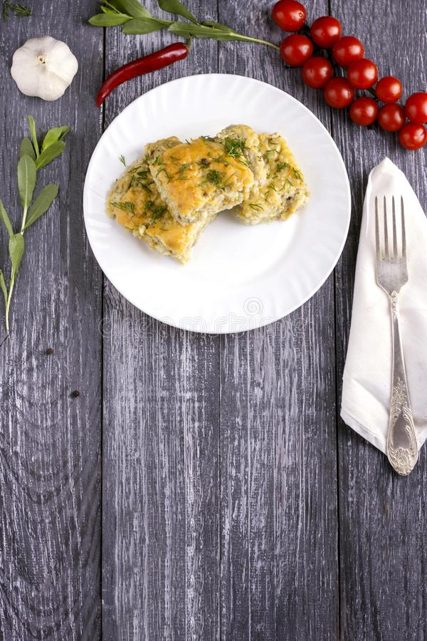 Delicious homemade casserole of zucchini, rice and cheese on a white plate on a wooden background royalty free stock photography
