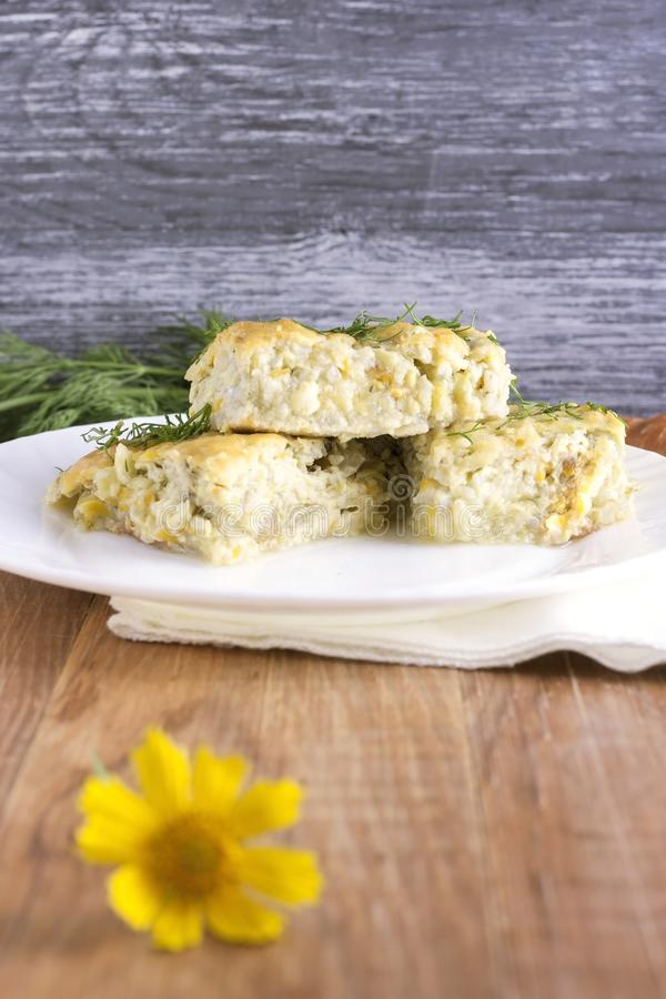 Delicious homemade casserole of zucchini, rice and cheese on a white plate on a wooden background stock images