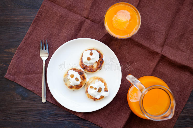 Delicious homemade cheese pancakes with fresh carrot juice royalty free stock photography