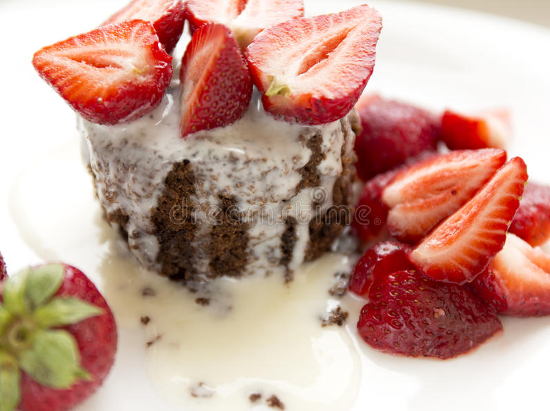 Delicious homemade chocolate cake with fresh red strawberries and cream sauce on white plate. royalty free stock photos