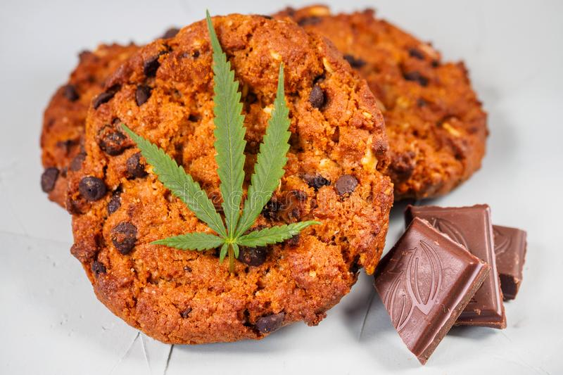 Delicious homemade Chocolate chip Cookies with CBD cannabis and. Leaf garnish and buds. Medicinal Edibles. Treatment of medical marijuana for use in food stock photo