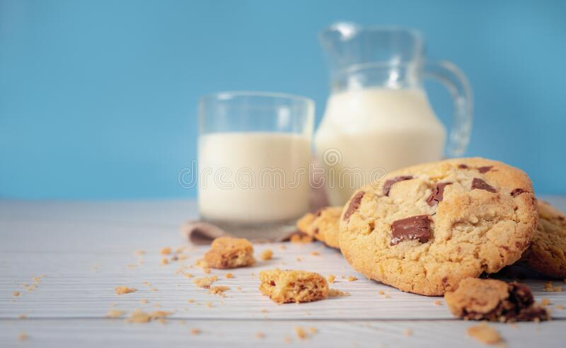 Delicious homemade chocolate chip cookies, paired with fresh milk in a glass and pitcher, placed on a white wooden floor and a royalty free stock photography