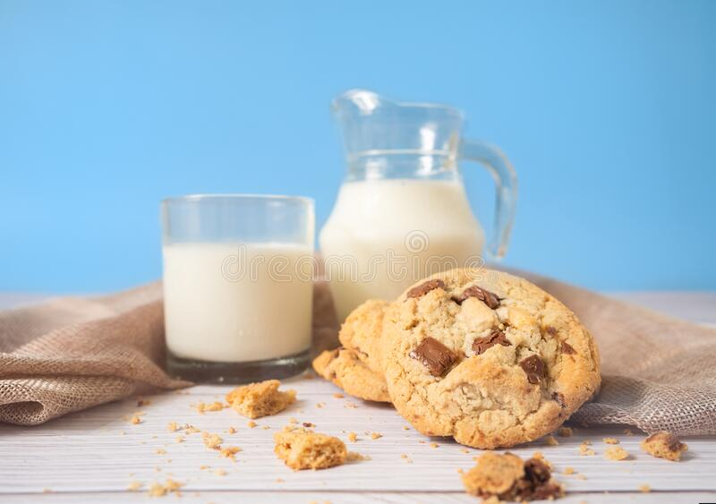 Delicious homemade chocolate chip cookies, paired with fresh milk in a glass and pitcher, placed on a white wooden floor and a stock photos