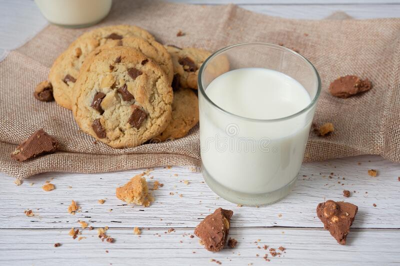 Delicious homemade chocolate chip cookies, paired with fresh milk in a glass and pitcher, placed on a white wooden floor and a stock photo