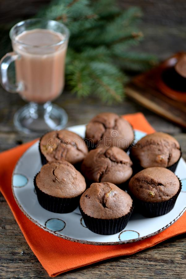 Delicious homemade chocolate muffins with cocoa and raisins on an old wooden background. royalty free stock photo