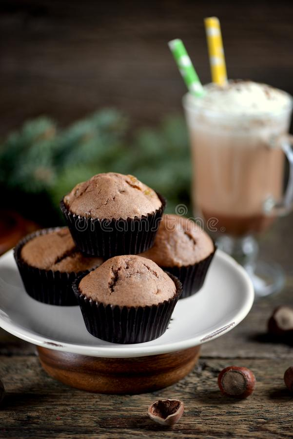 Delicious homemade chocolate muffins with cocoa and raisins on an old wooden background. royalty free stock image