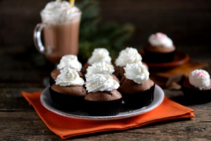 Delicious homemade chocolate muffins with cocoa and raisins on an old wooden background. stock images