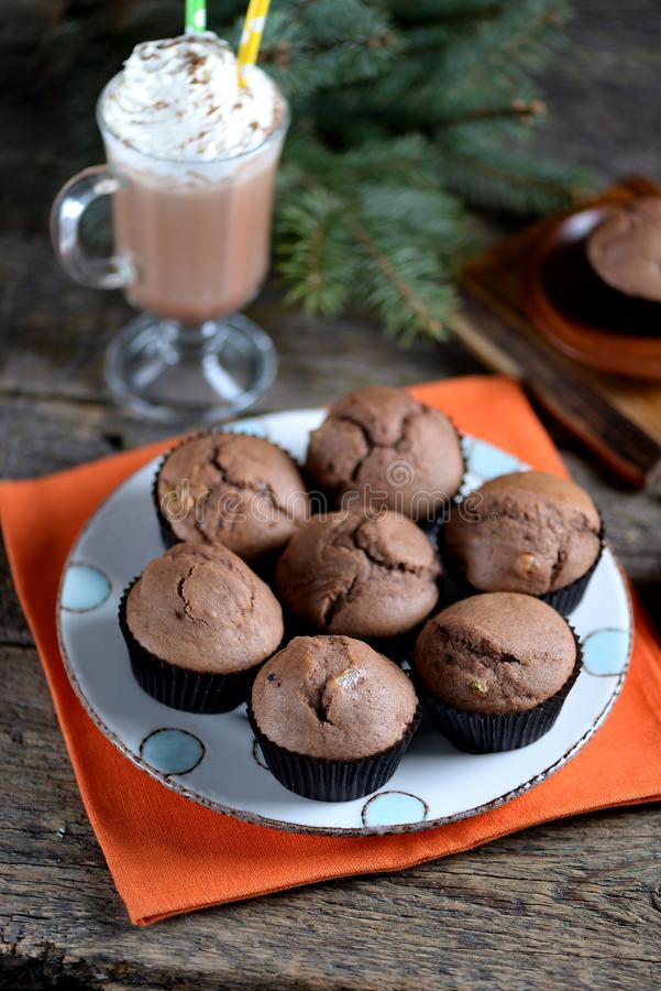 Delicious homemade chocolate muffins with cocoa and raisins on an old wooden background. royalty free stock images
