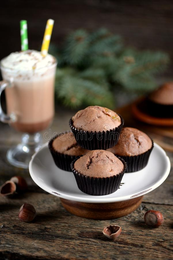 Delicious homemade chocolate muffins with cocoa and raisins on an old wooden background. stock image