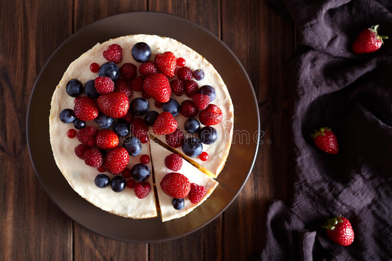 Delicious Homemade creamy mascarpone New York Cheesecake with berries on dark wooden table. Top viev. stock images