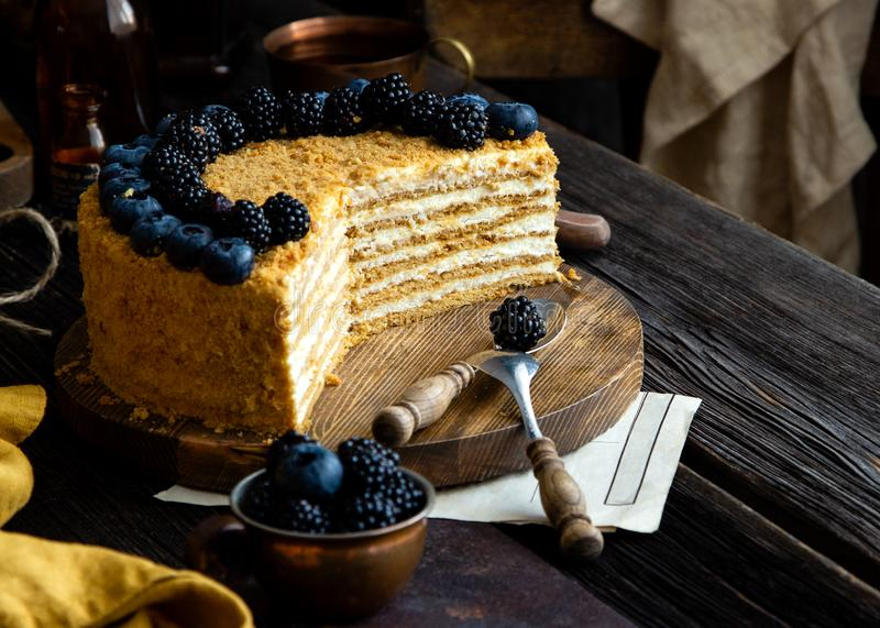 Delicious homemade cut of russian honey cake medovik with white cream, blue and black berries on top. On wooden stand on rustic table with copper cup of berries stock photos