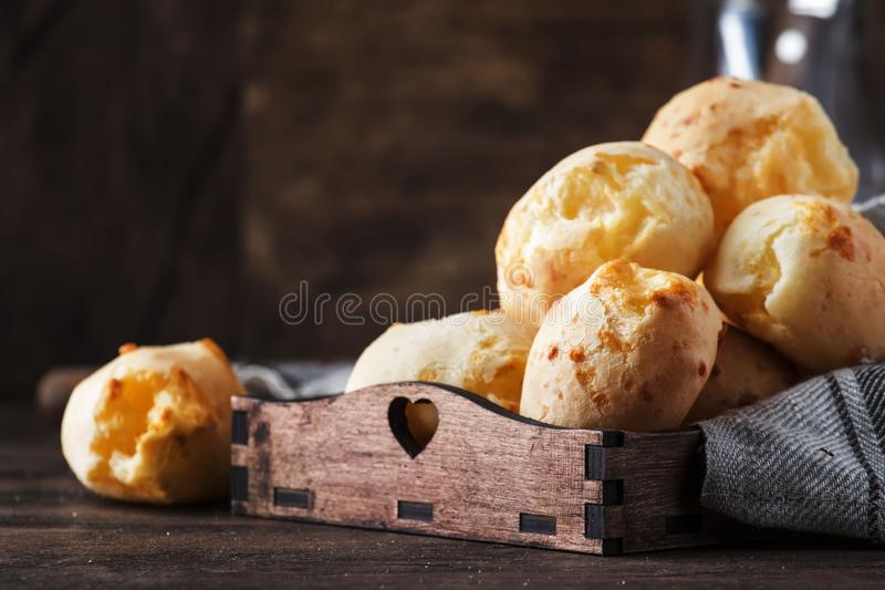 Delicious homemade golden cheese savory buns in tray, vintage wooden rustic table background, selective focus stock image