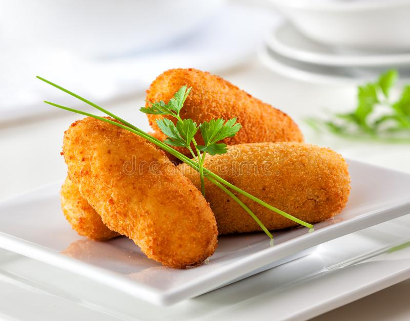Traditional Spanish croquettes or croquetas served on a white plate. royalty free stock images