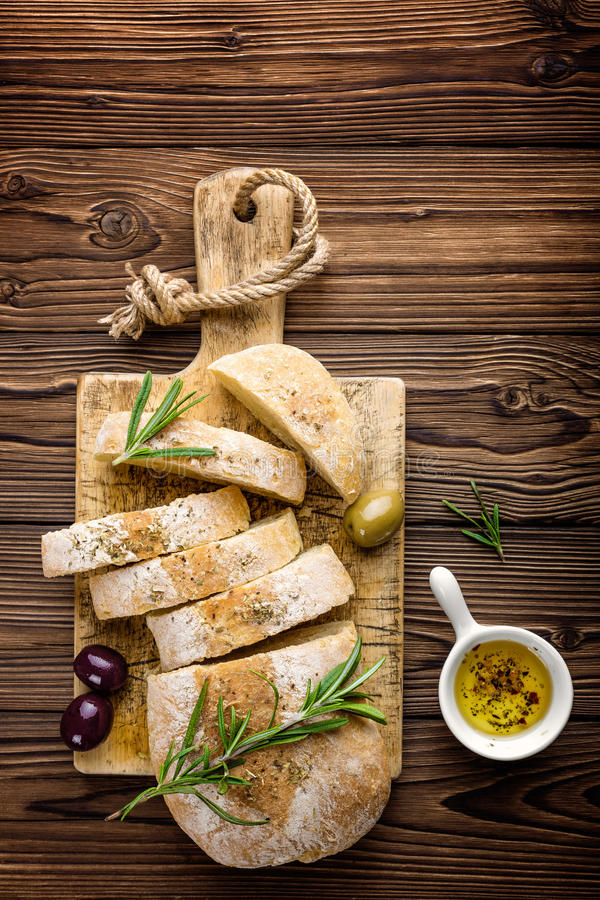 Delicious homemade italian ciabatta bread with olive oil and olives on wooden rustic background, above view, space for text royalty free stock images