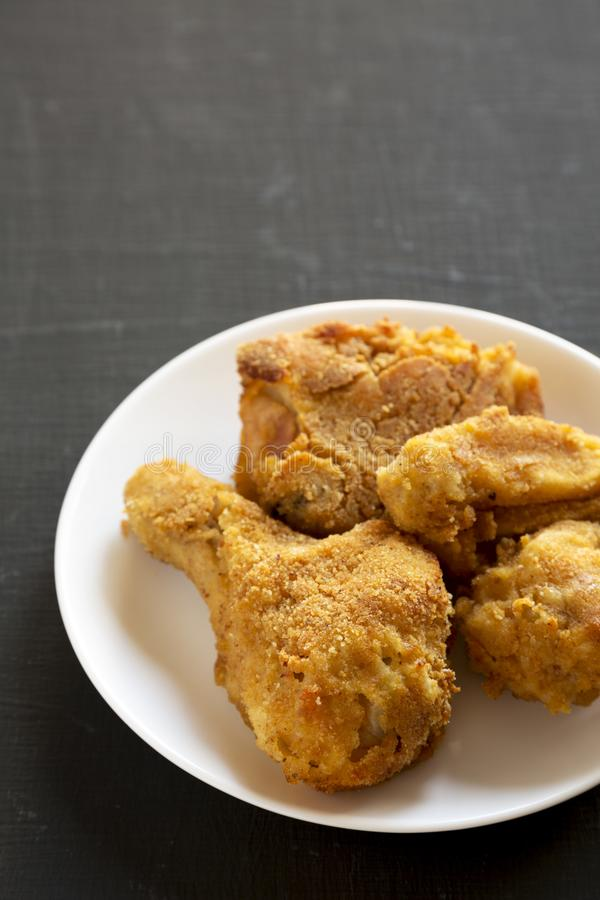 Delicious homemade oven baked fried chicken on a white plate over black background, low angle view. Copy space.  royalty free stock photos