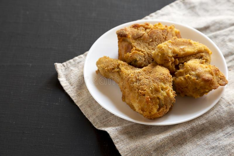 Delicious homemade oven baked fried chicken on a white plate over black surface, low angle view. Copy space.  royalty free stock photo