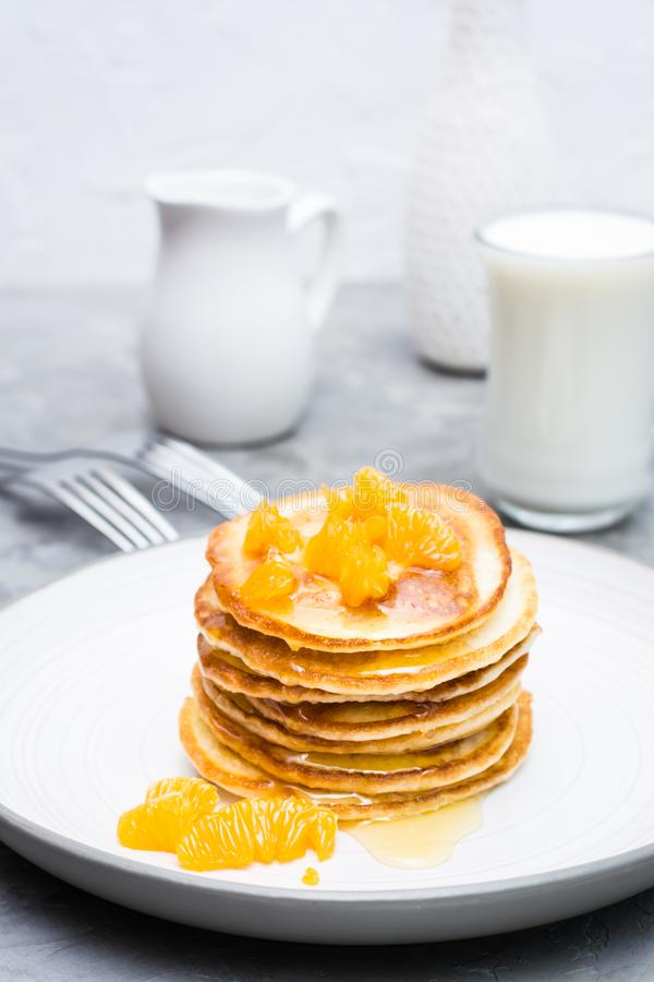 Delicious homemade pancakes with tangerines and honey, glass of milk on a plate royalty free stock photography