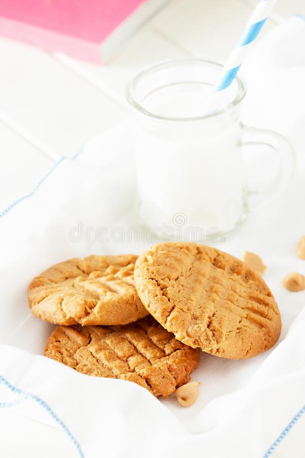Delicious homemade peanut butter cookies with mug of milk. White wooden background. Healthy snack or tasty breakfast concept stock photos