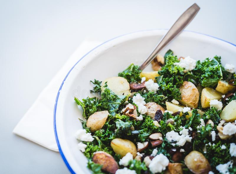 Delicious homemade roast potato, kale and feta cheese salad with nuts. royalty free stock images