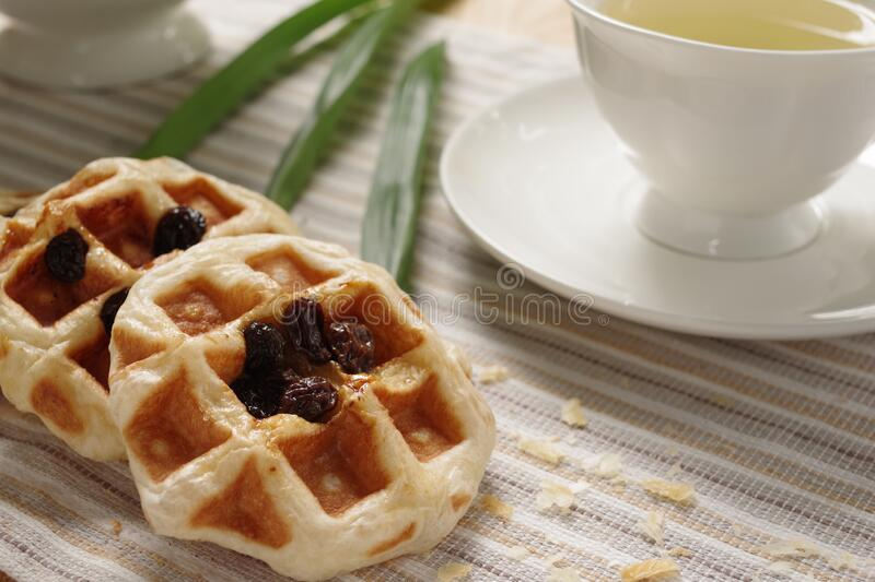 Tasty homemade rum raisin waffles with earl grey in the afternoon tea. royalty free stock images
