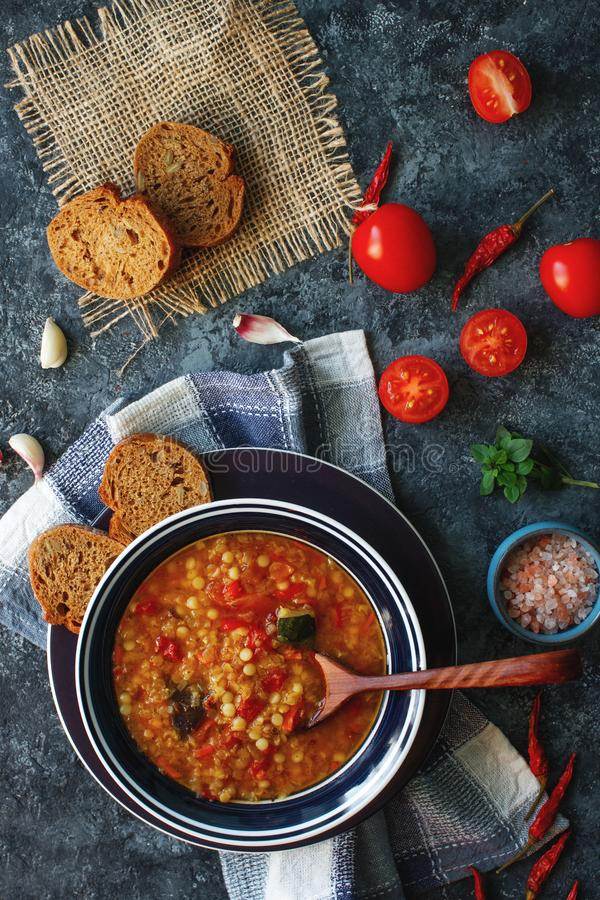 Delicious homemade soup from organic red lentil, vegetables, basil, garlic and piece of black bread on dark stone table. Healthy l royalty free stock photo