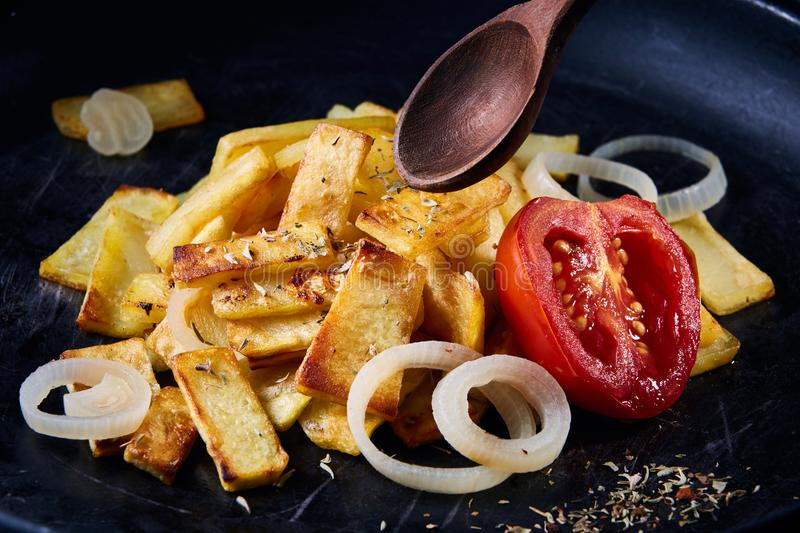 Delicious homemade spicy fries with onion and grilled tomato over dark background, selective focus royalty free stock images