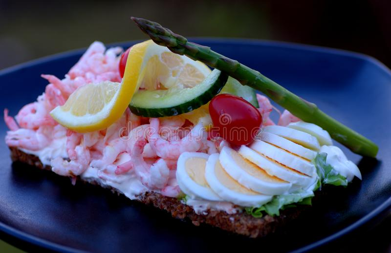 A delicious homemade spicy shrimp sandwich with eggs, citrea, tomatoes, asparagus and sallad stock images