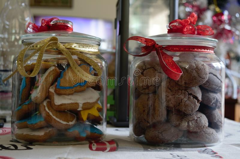 Delicious homemade tasty christmas cookies and in a beautiful decorated jar and a christmas tree and a candle in the back royalty free stock photos