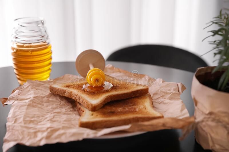 Delicious honey and toasts. On black table royalty free stock photo