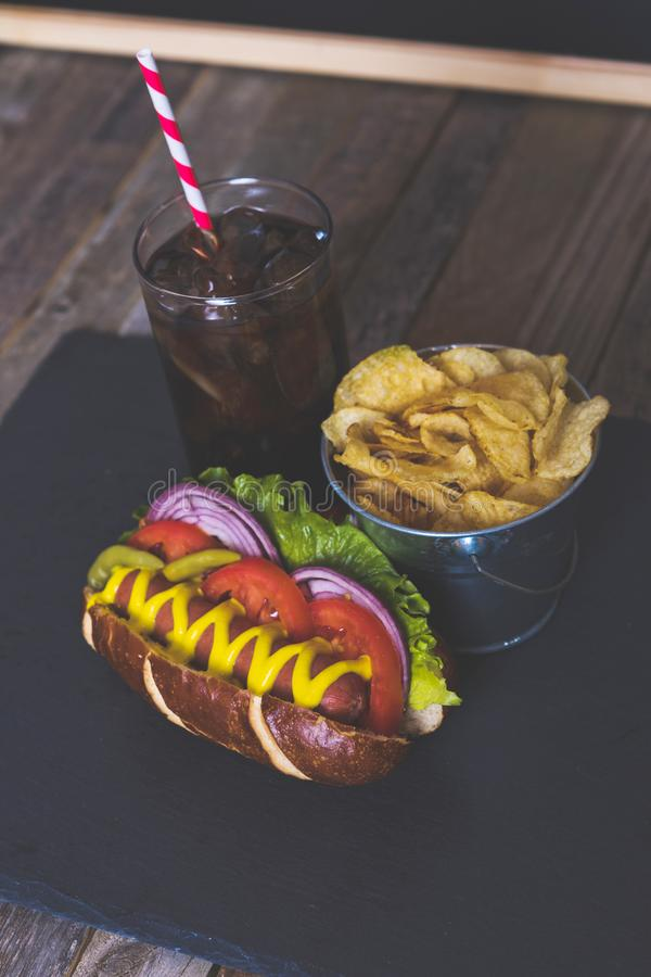 Delicious hot dog with toppings on dark background. Tabletop, side view stock image