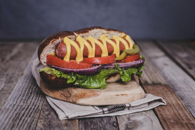Delicious hot dog with toppings on dark wooden background. Tabletop, front view royalty free stock photo