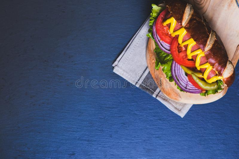 Delicious hot dog with toppings on dark wooden background. Tabletop, top view stock photo