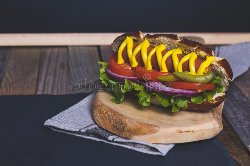 Delicious hot dog with toppings on dark wooden background. Tabletop, front view royalty free stock photography