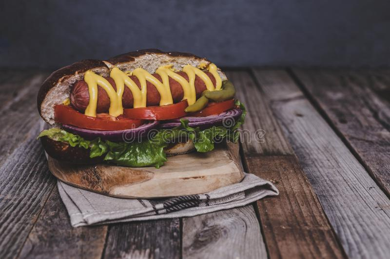 Delicious hot dog with toppings on dark wooden background. Tabletop, front view stock photography