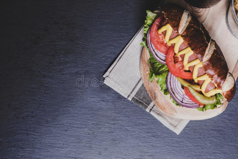 Delicious hot dog with toppings on dark wooden background. Tabletop, top view royalty free stock images