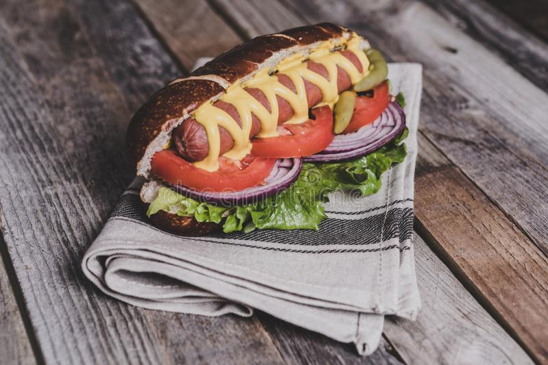 Delicious hot dog with toppings on dish cloth and wooden background. Tabletop, side view stock photo