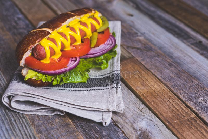 Delicious hot dog with toppings on dish cloth and wooden background. Tabletop, side view royalty free stock images