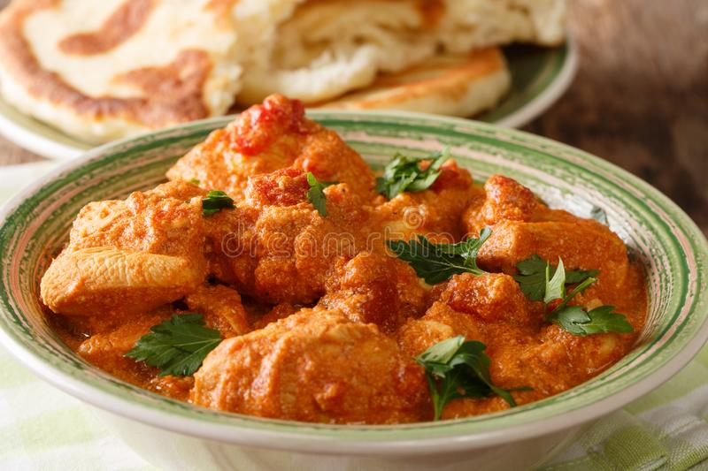 Delicious hot Indian Karhai chicken in a spicy sauce close-up served with fresh naan bread. horizontal stock photo