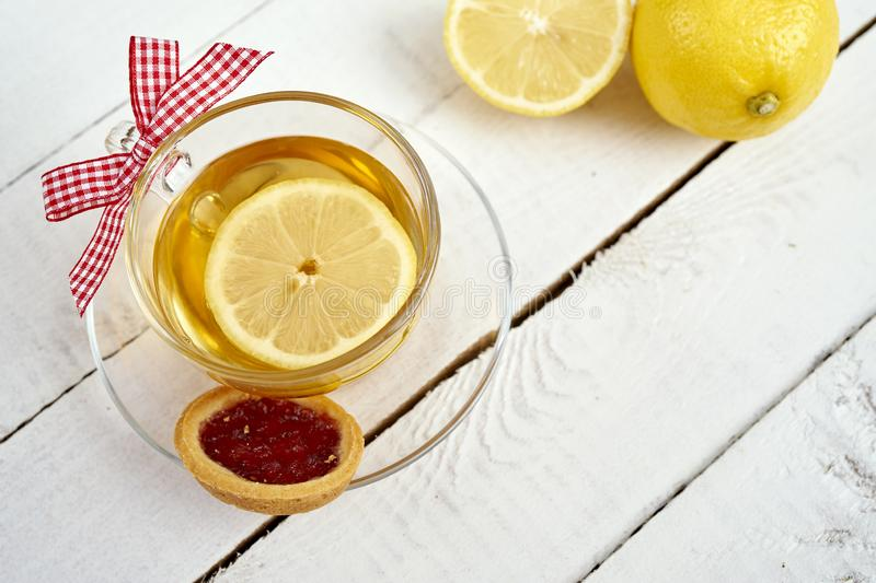 Delicious hot tea with honey with lemon and cookie on an old wooden table stock photography