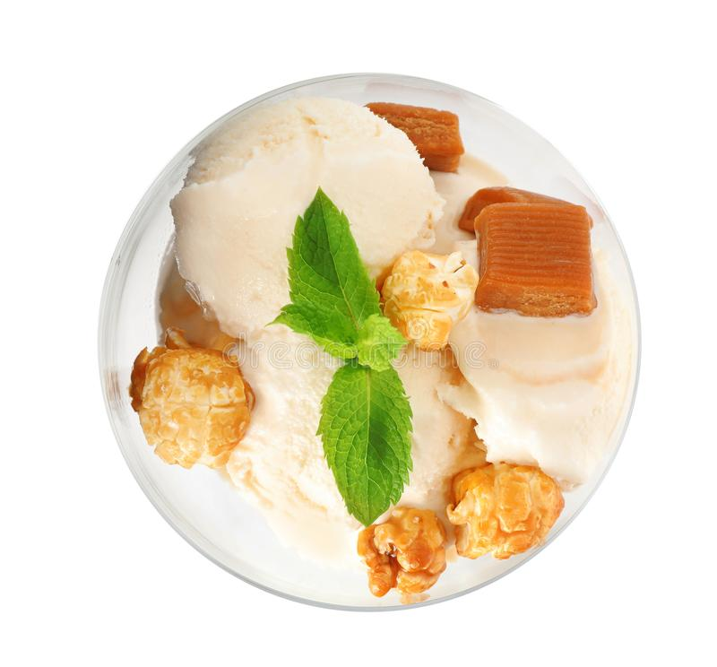 Delicious ice cream with caramel candies and popcorn in dessert bowl on white background. Top view stock images