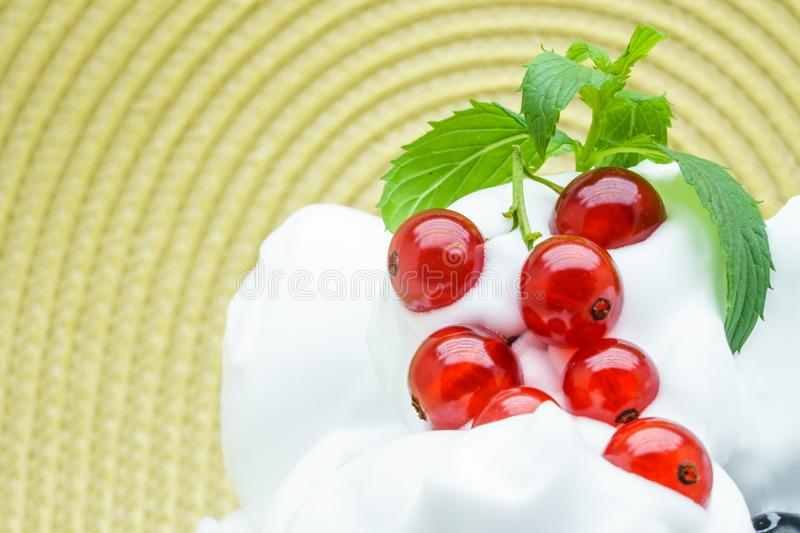 Delicious ice-cream with red currant. Ripe red currant and vanilla ice cream for a healthy refreshing cold summer royalty free stock photography