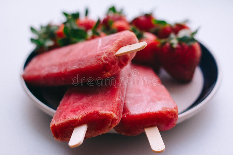 Delicious ice cream sticks with strawberries on a white background royalty free stock image