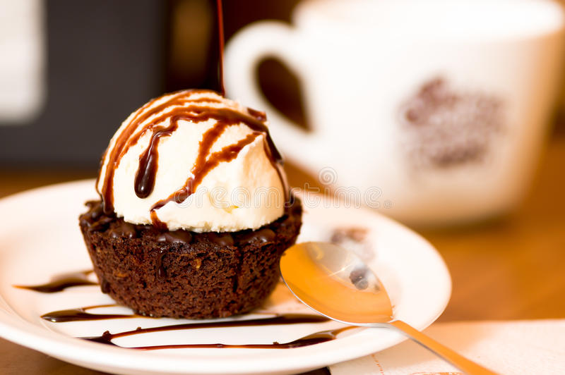 Delicious icecream on top of a brownie with a chocolate sauce in the plate.  royalty free stock images