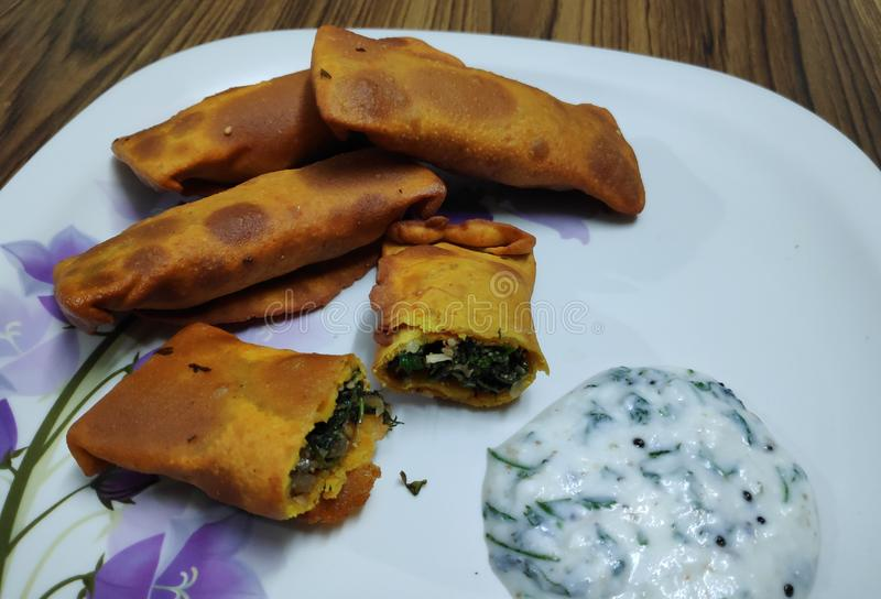 Delicious Indian snack called as kothimbir vadi seasoned with curd chutney. stock photos